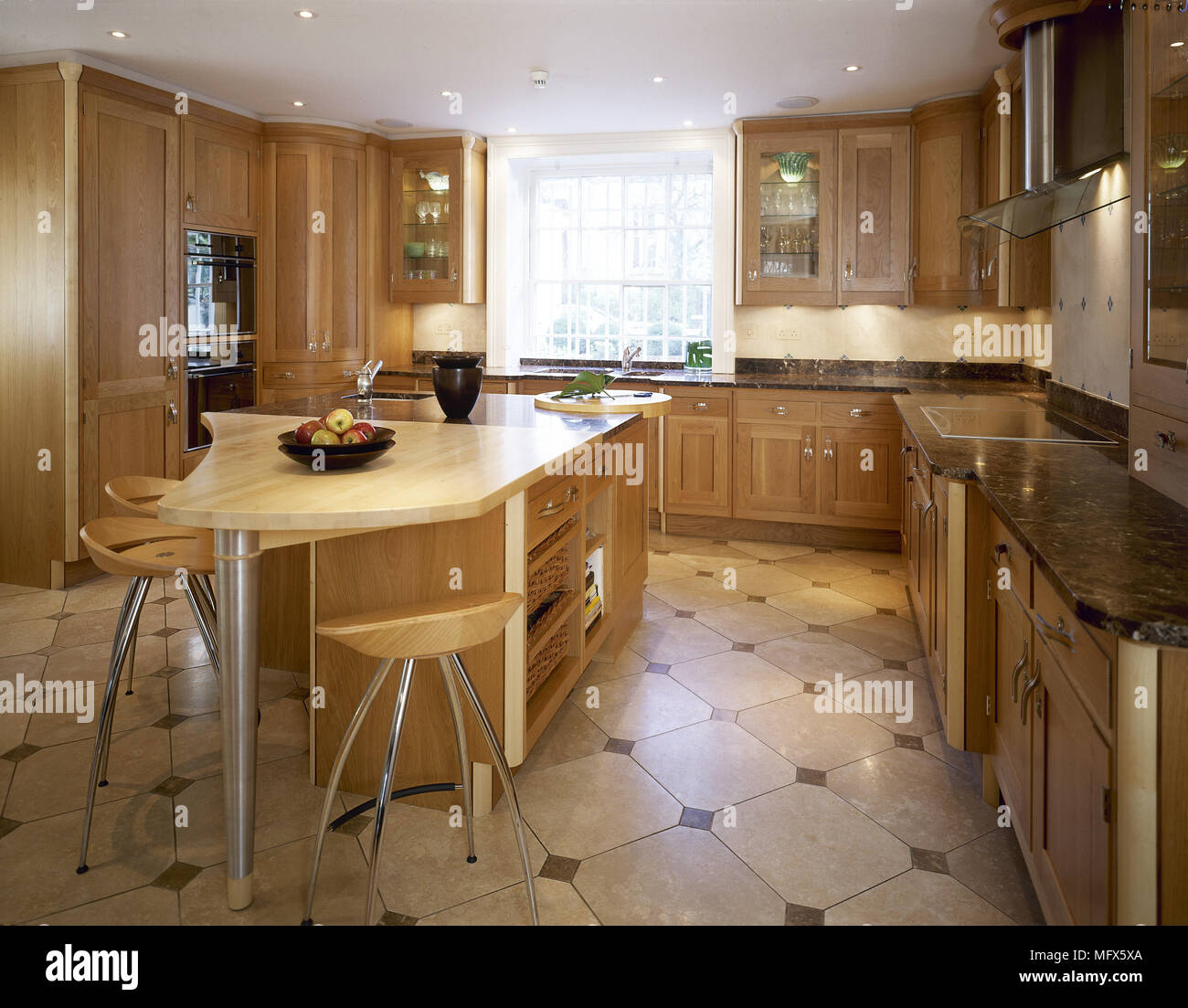 Modern kitchen with tiled floor, wooden cabinets, central island breakfast bar, and lit recessed lighting. - Stock Image