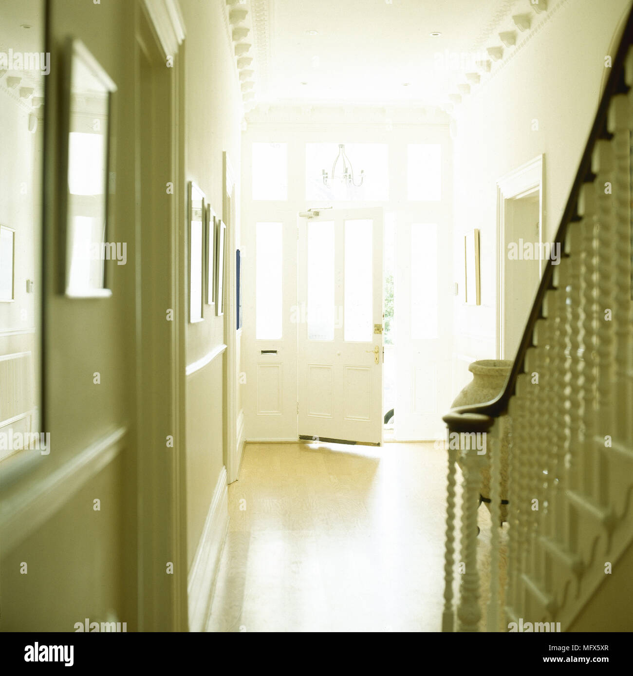 Traditional Entryway With A Tiled Floor Decorative Crown Moulding Staircase Railing And An Open Front Door Stock Photo Alamy