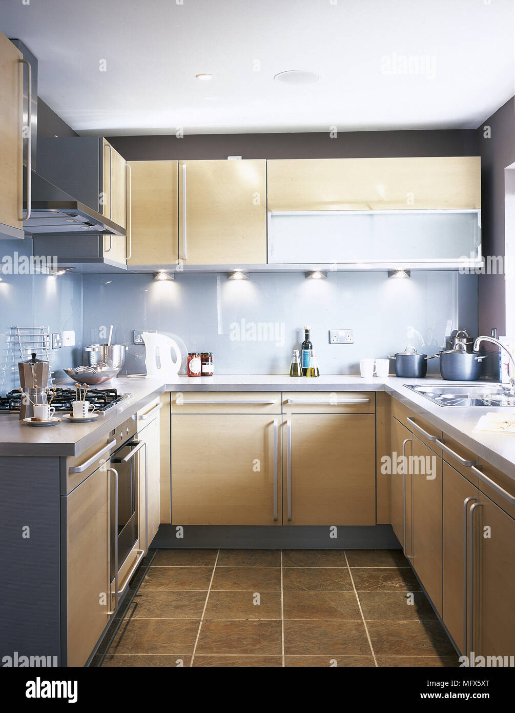 Modern galley kitchen with wooden cabinets under cabinet lighting modern galley kitchen with wooden cabinets under cabinet lighting and a tiled floor aloadofball Image collections