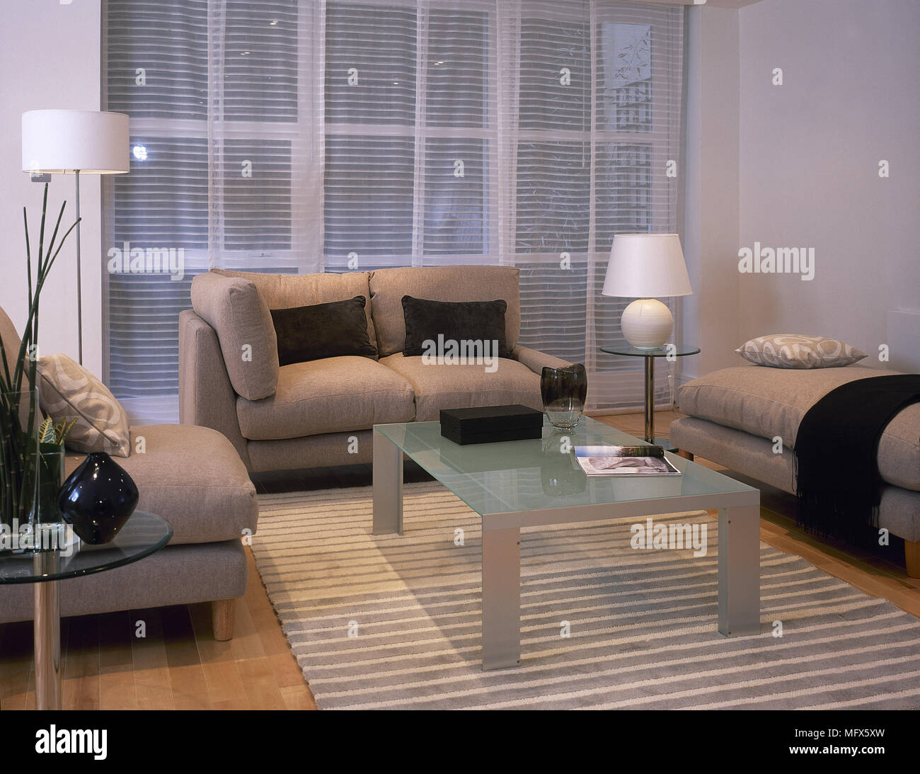 Modern Sitting Room With An Overstuffed Sofa And Chaise, Glass Top Coffee  Table, Area Rug, And Sheer Curtains Over The Window.