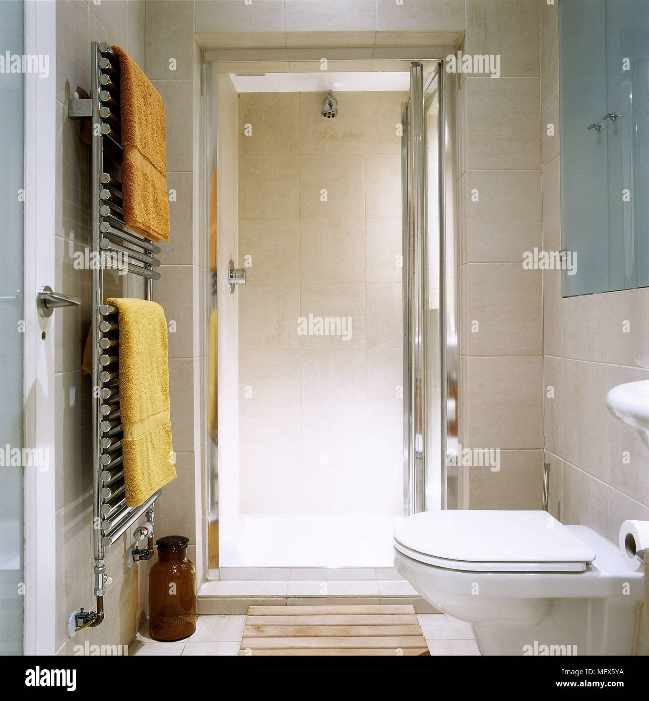 Modern, tiled bathroom with a shower cubicle, toilet, and towels ...