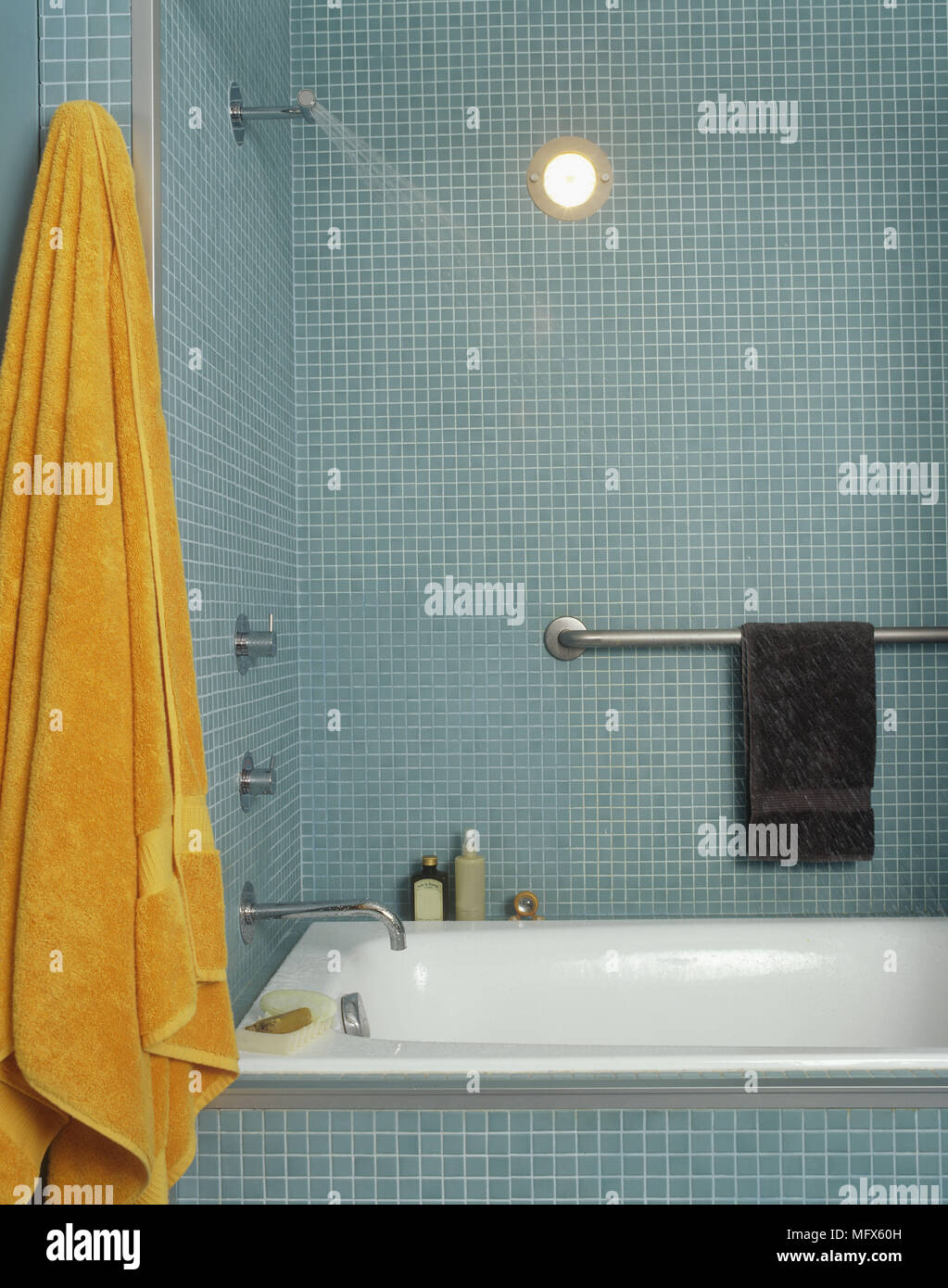 A modern blue bathroom tiled walls with mosaic tiles bath chrome tap ...