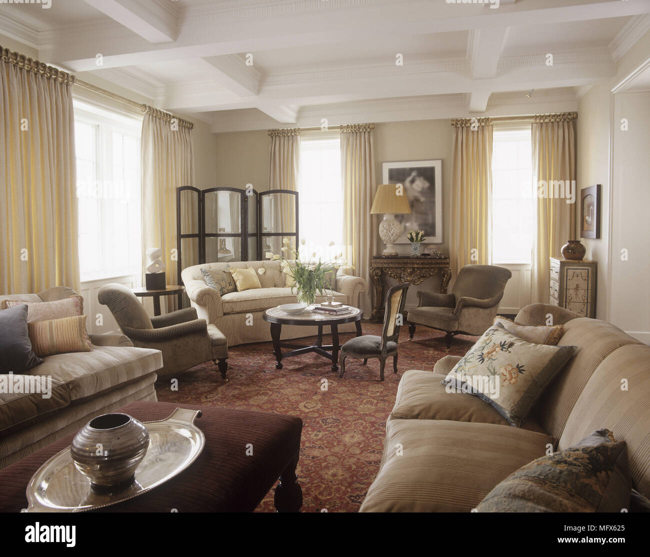 . A traditional sitting room with sofas and chairs beamed ceiling