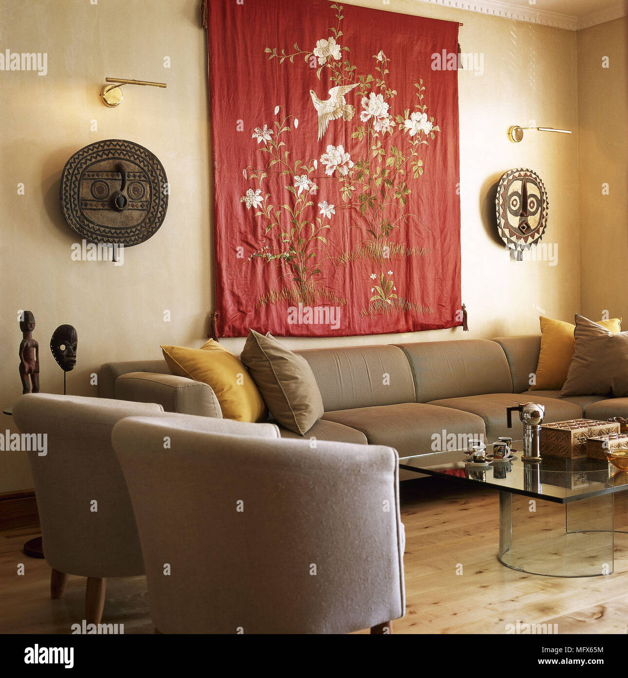 Neutral Sitting Room With Tub Armchairs Sofa Embroidered Fabric Wall Hanging And Exotic Art Pieces Stock Photo Alamy