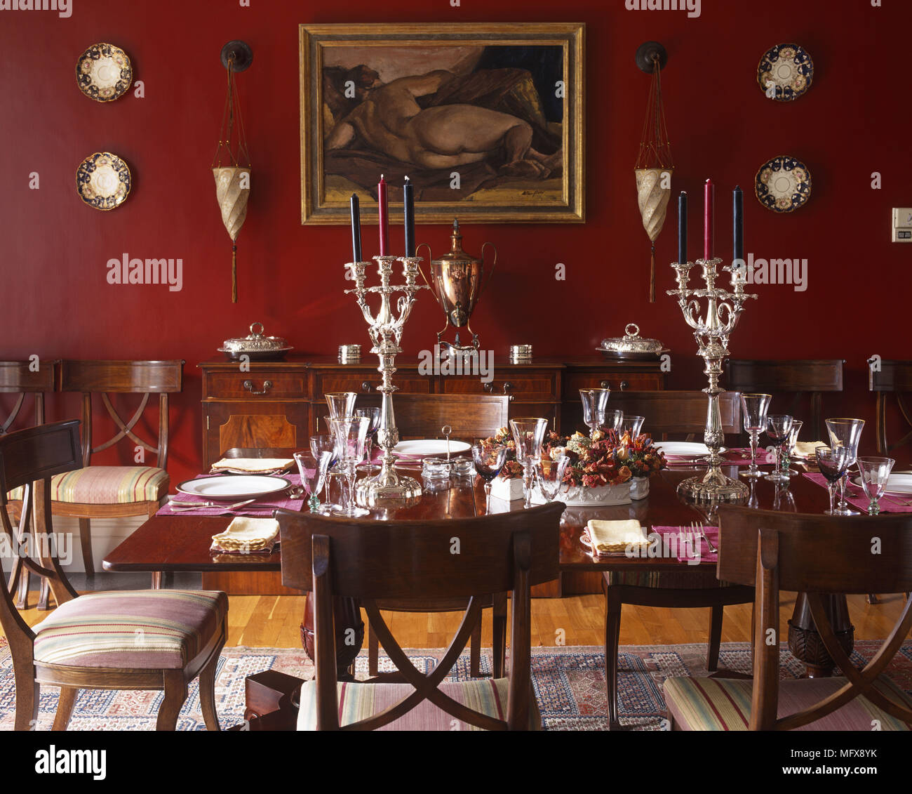 Silver Candlesticks On Table Set For Dinner In Traditional Style Red Dining Room Stock Photo Alamy
