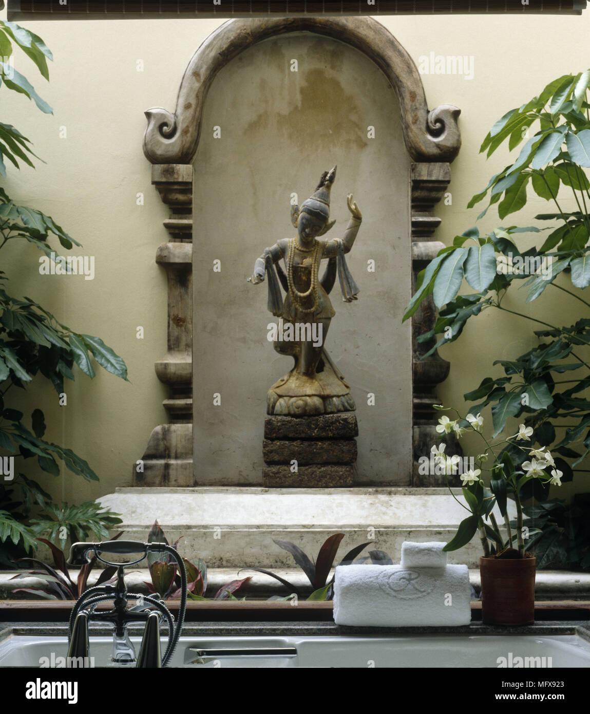 Far Eastern style figurine behind bathtub - Stock Image