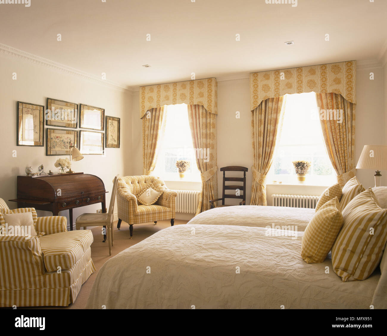 Pair of single beds and armchairs in yellow bedroom Stock ...