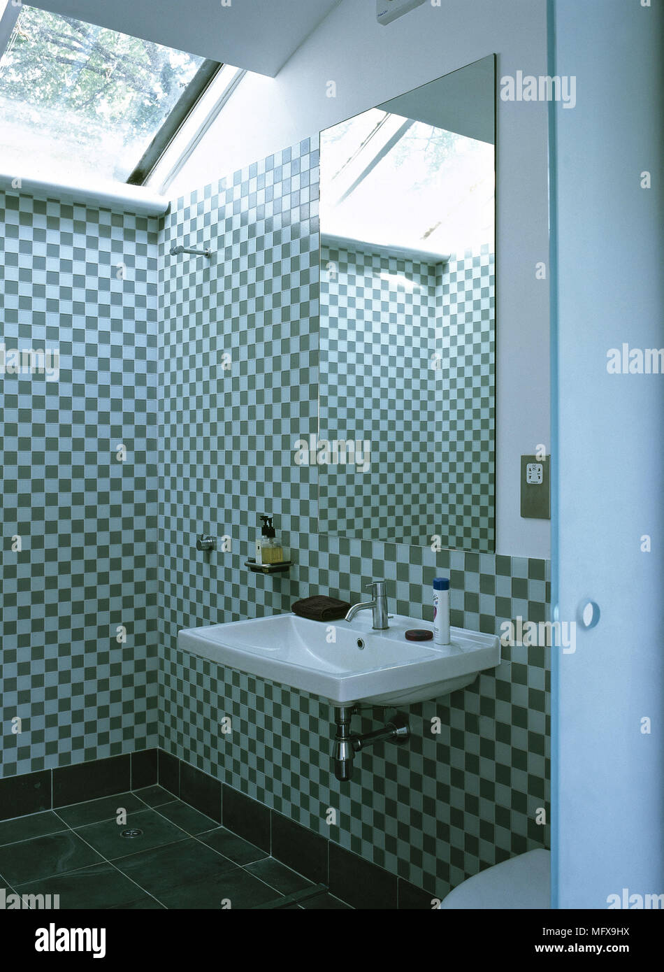 Bathroom with washbasin and shower area with check patterned mosaic ...