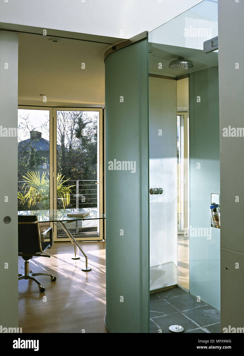View through bathroom with glass shower cubicle to home office Stock ...