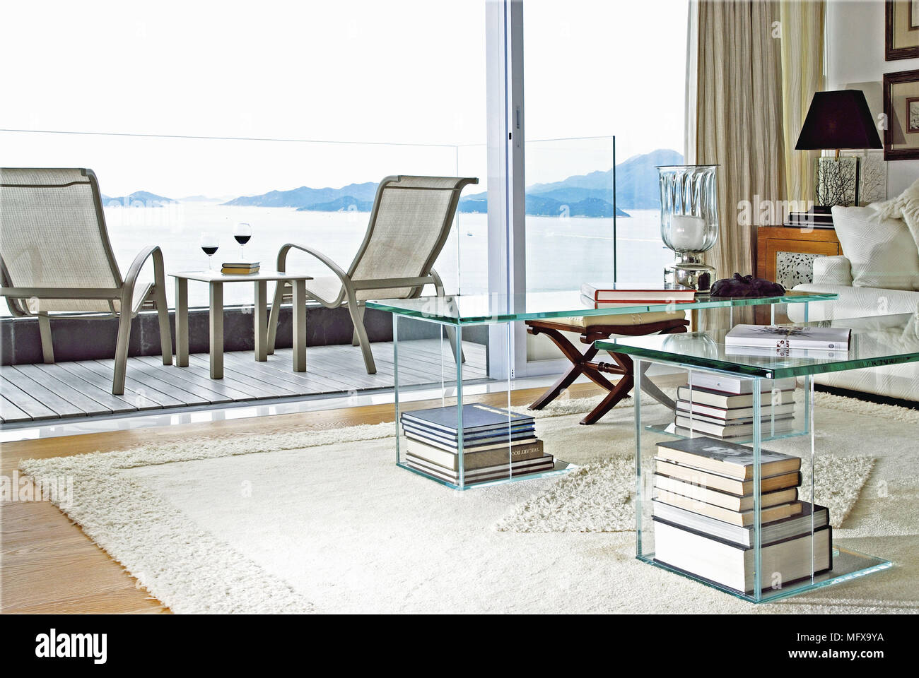 ec950ce07ff4 Transparent tables in modern sitting room with view to balcony terrace