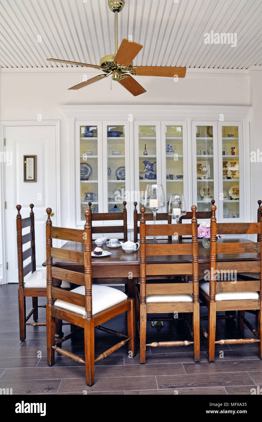 Ceiling fan above wooden table and chairs in traditional style dining room Stock Photo