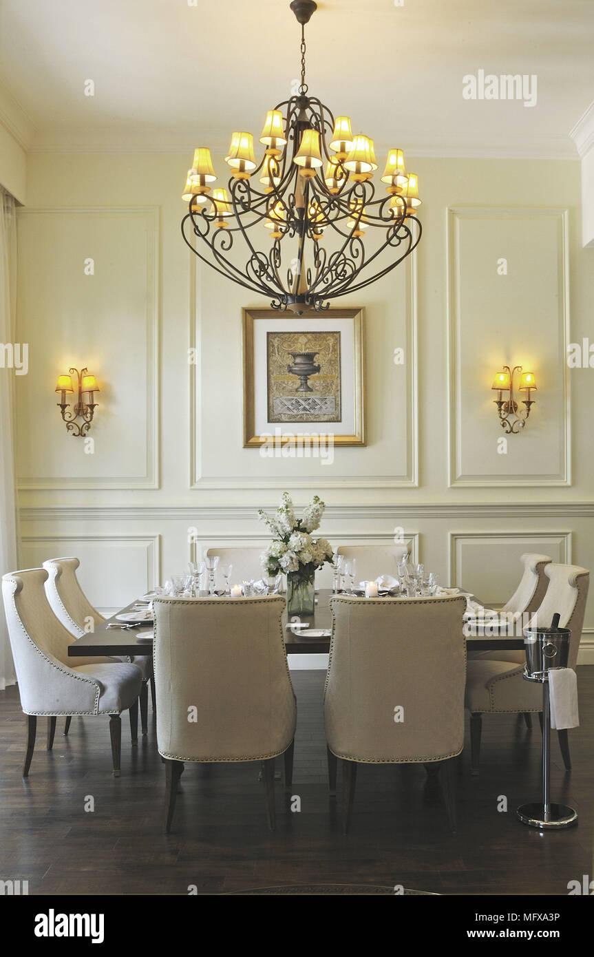 Chandelier above table and chairs in traditional style ...