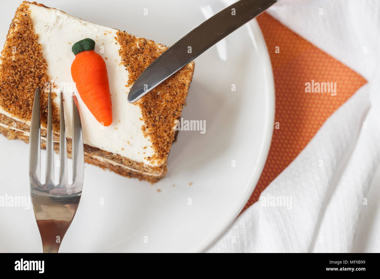Homemade carrot cake with carrot decorations on white plate, fork, knife, napkin, top view. - Stock Image
