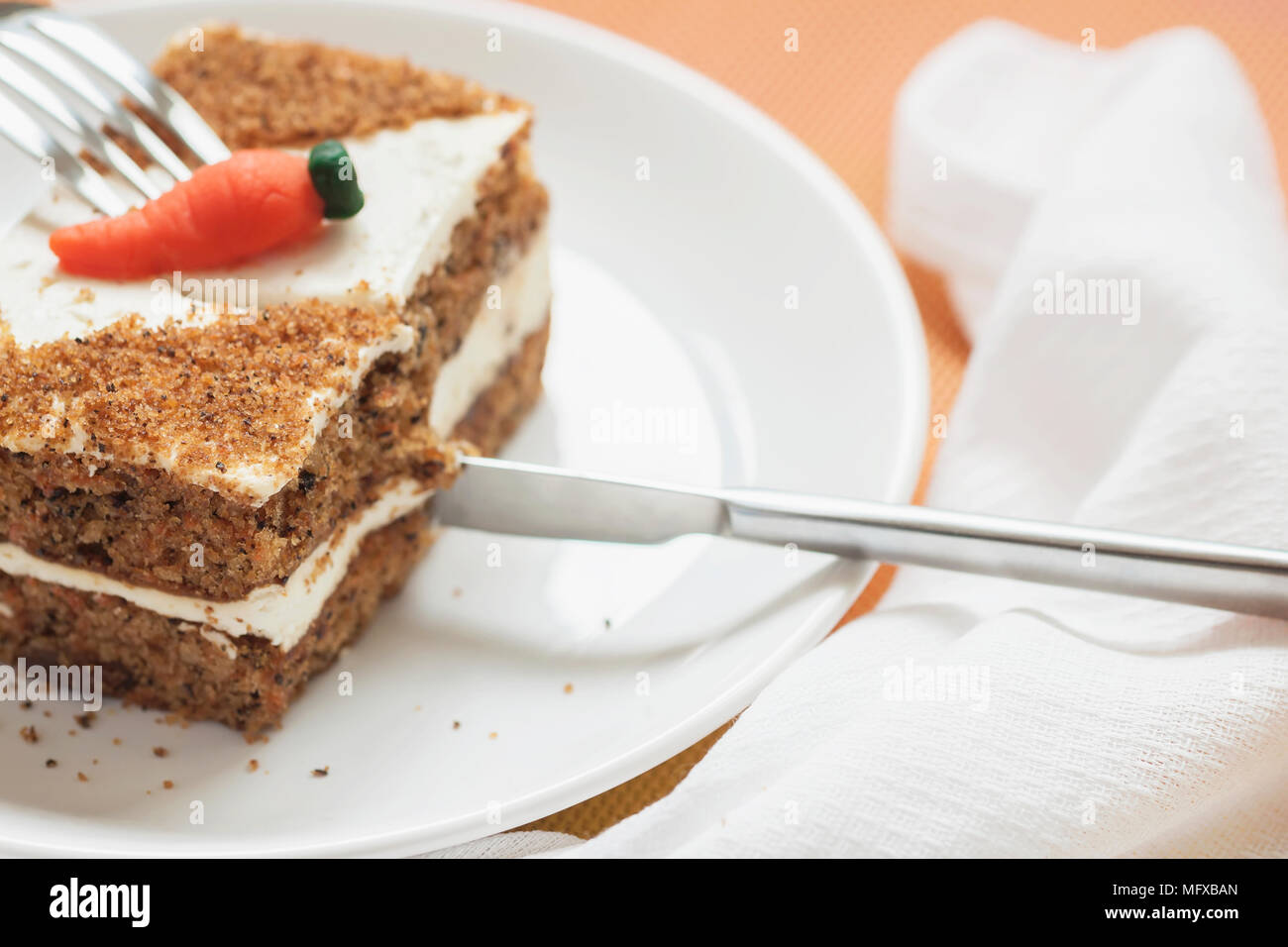 Slice of home made carrot cake, white plate, napkin. Knife cuts an appetizing piece. Sweet healthy vegan food. Selective focus, copy space - Stock Image