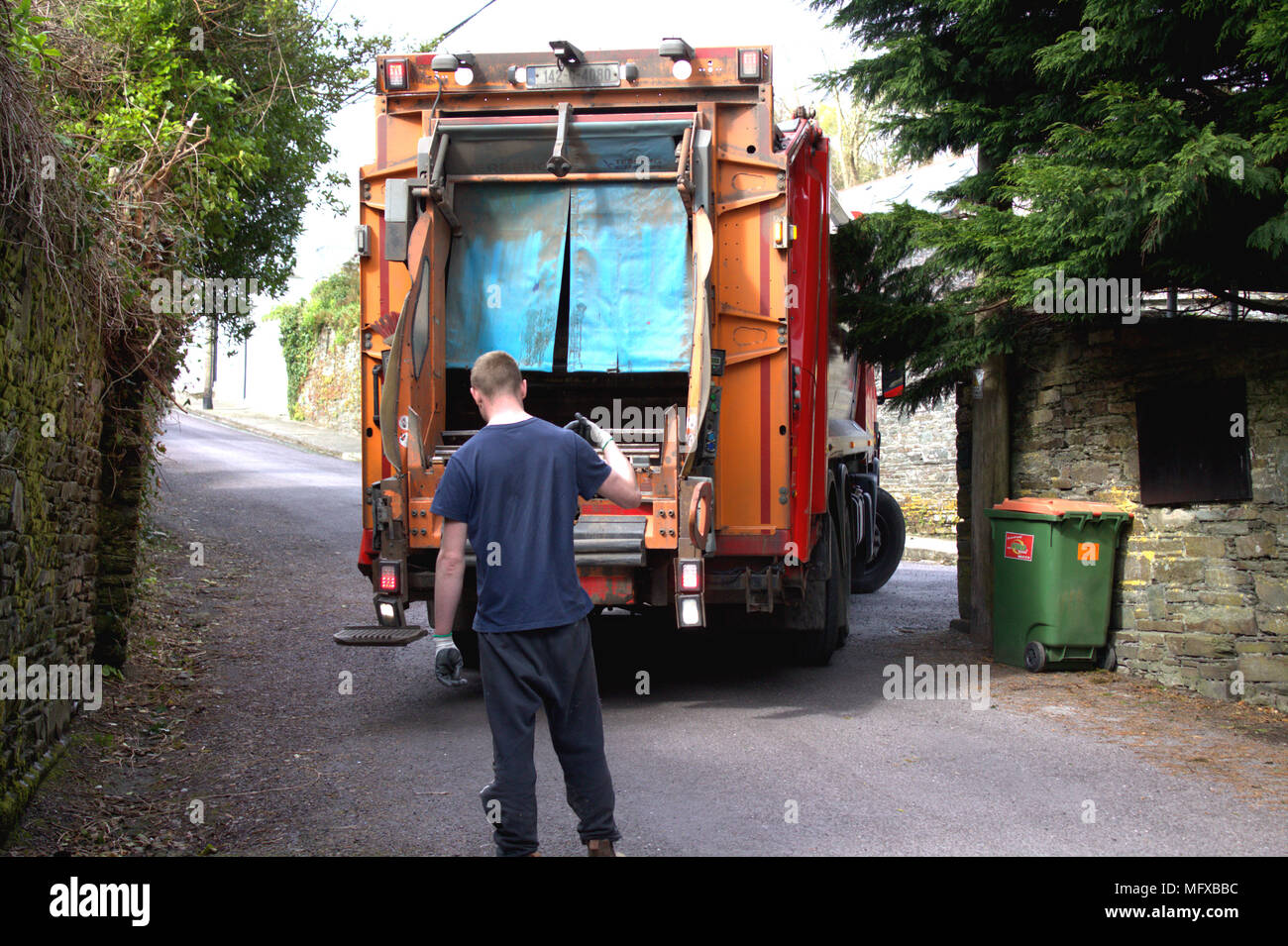 young adult male guiding a garbage bin collection lorry, truck that is reversing into a narrow road, prior to collecting the rubbish, garbage. - Stock Image