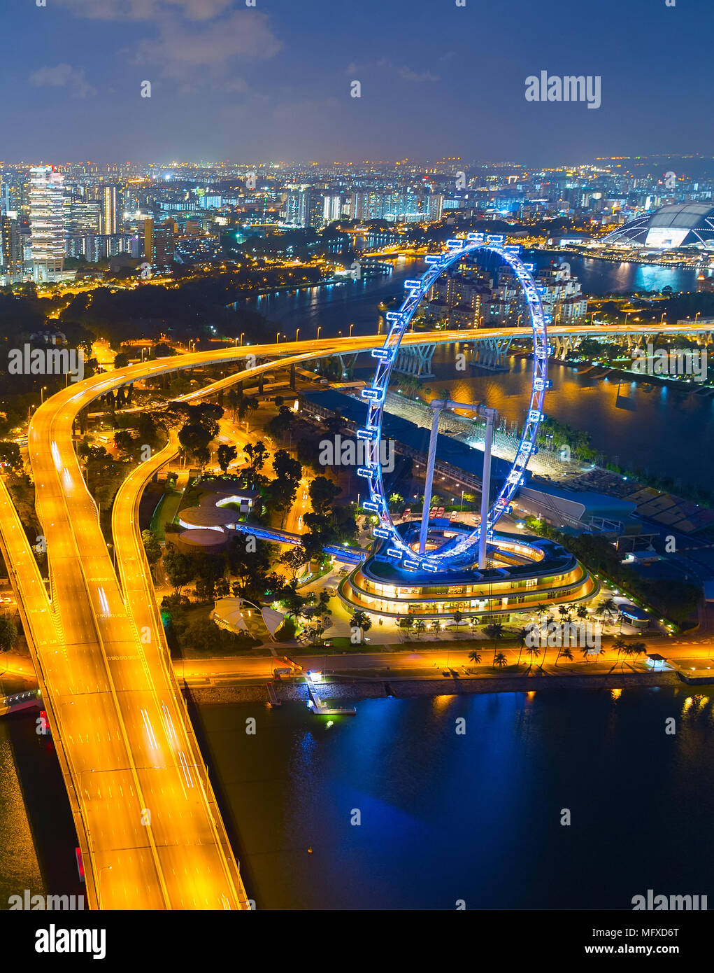 Skyline of Singapore with famous Singapore Ferries Wheel at twilight - Stock Image