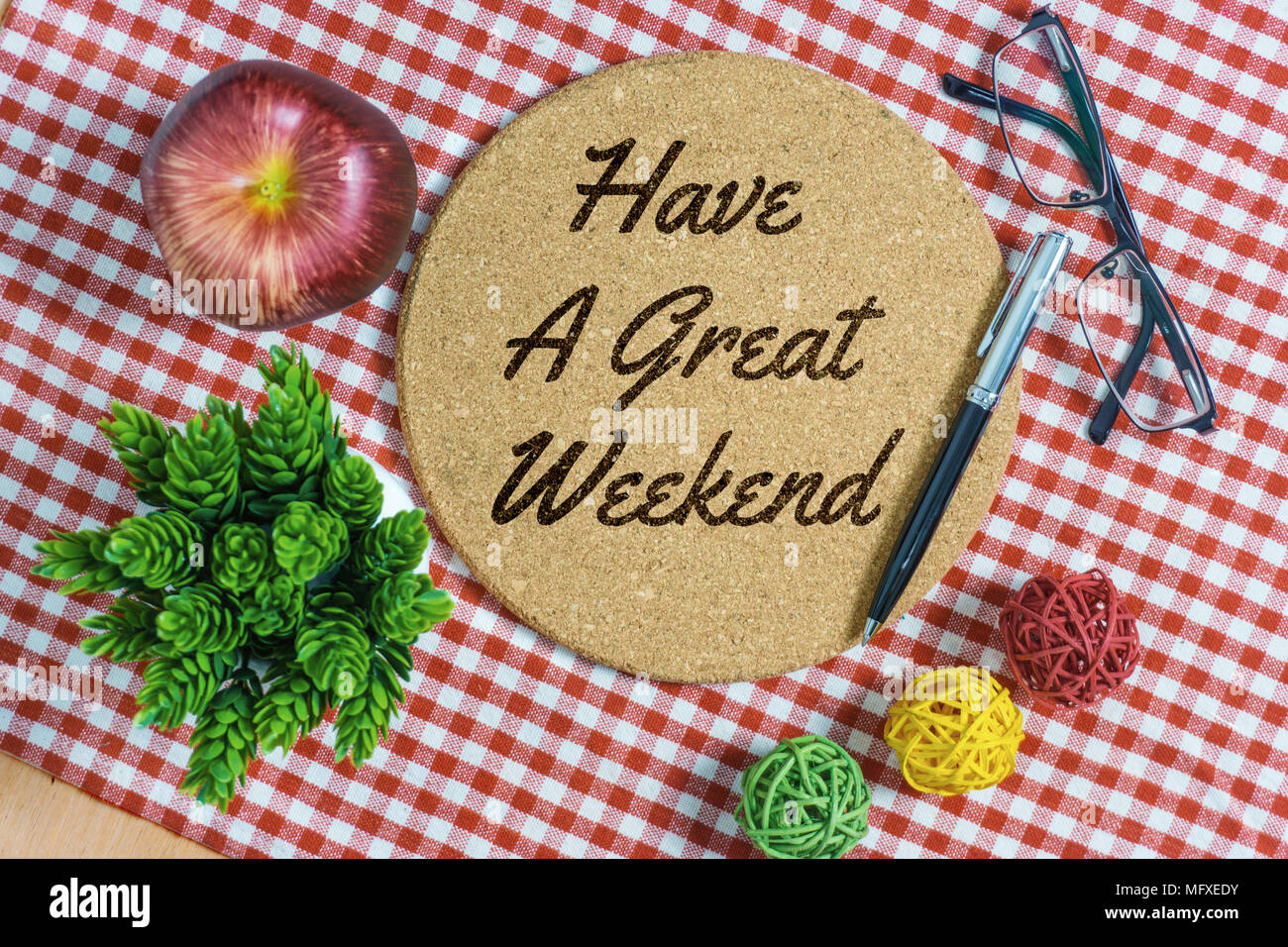 Have A Great Weekend. Cork bulletin board on red stripes napkin with pen, apple, spectacle and potted plant. - Stock Image