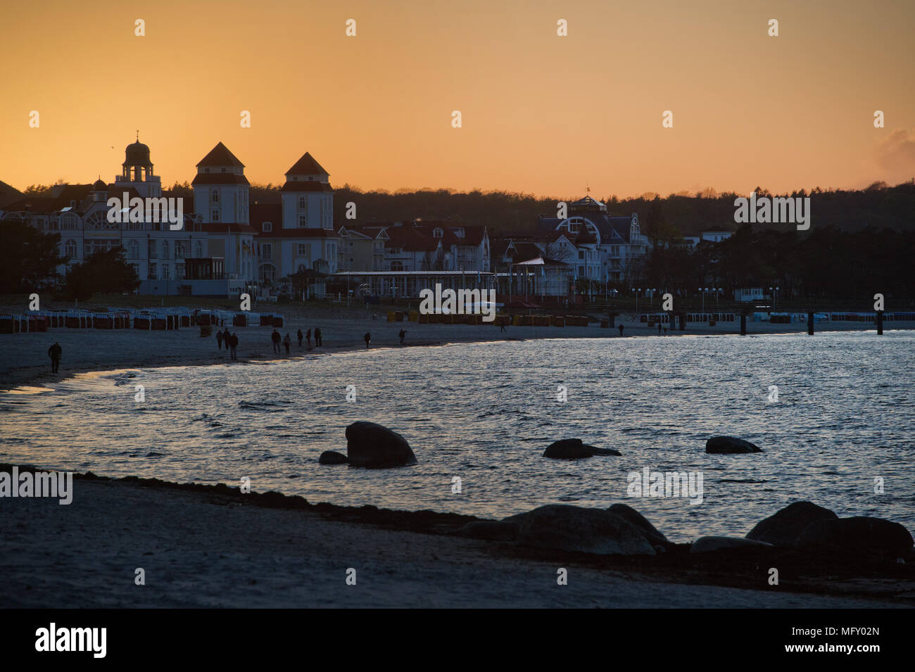 26 April 2018, Germany, Binz: Vacationers walking at sunrise along a beach in the Baltic resort on the Baltic Sea island of Ruegen. The island of Ruegen's economy is mainly geared to tourism. Photo: Stefan Sauer/dpa-Zentralbild/dpa - Stock Image