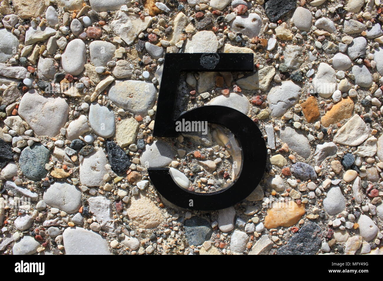 The number five as a black plastic text glued to a textured pebble concrete wall. - Stock Image