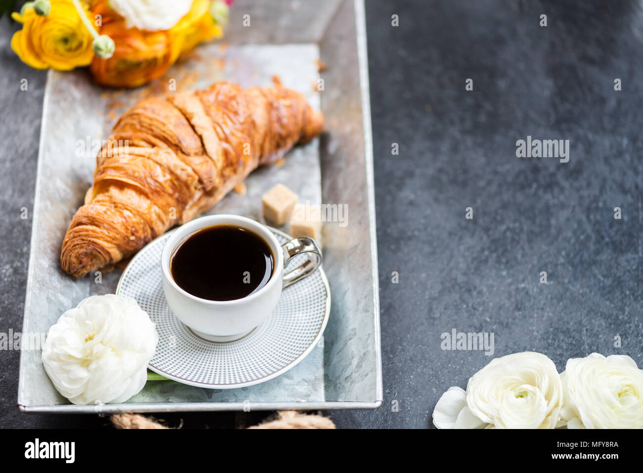 Light Breakfast from fresh Croissant and Cup of Coffee on the grey tray, Ranunculus Flowers nearby - Stock Image