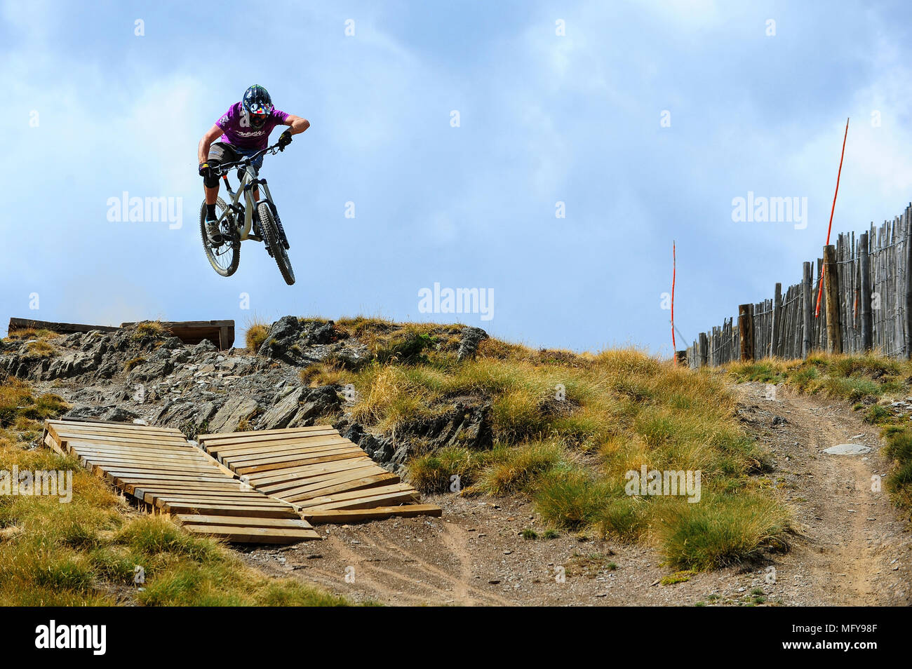 A man rides a mountain bike in the Grandvalira resort in Andorra in the Pyrenees. - Stock Image