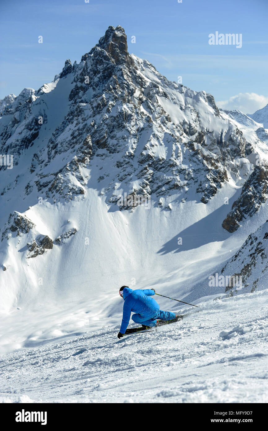 A skier carves a turn on piste in front of the Aiguille du Fruit mountain in the French alpine resort of Courchevel. Stock Photo