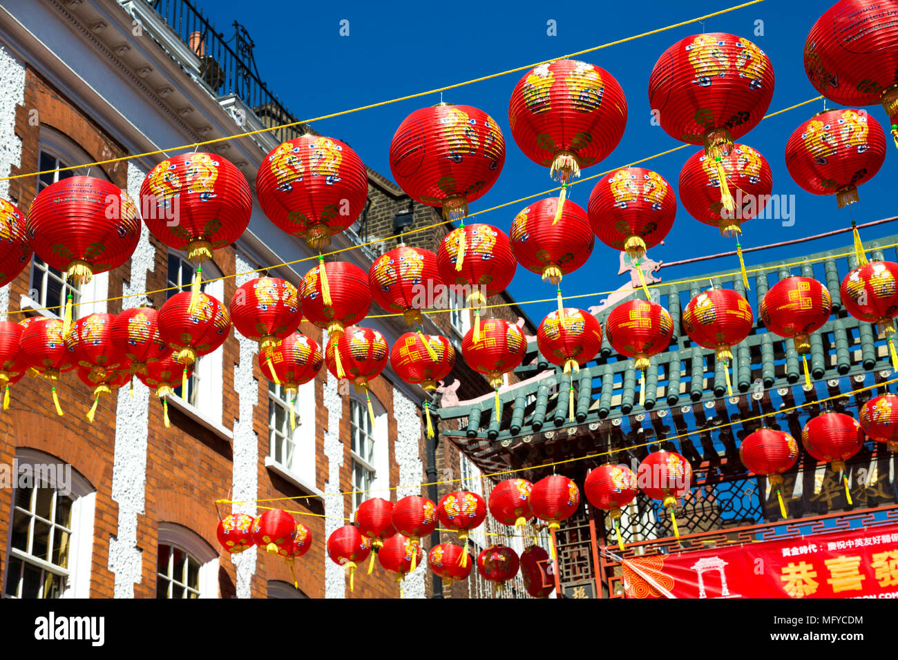 Red and yellow Chinese lanterns hanging above a street in China Town, London, UK - Stock Image