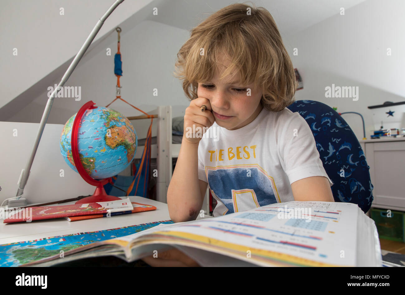 Boy, elementary school student, 8 years old, learns for school at home, does homework, Mathematics, Stock Photo
