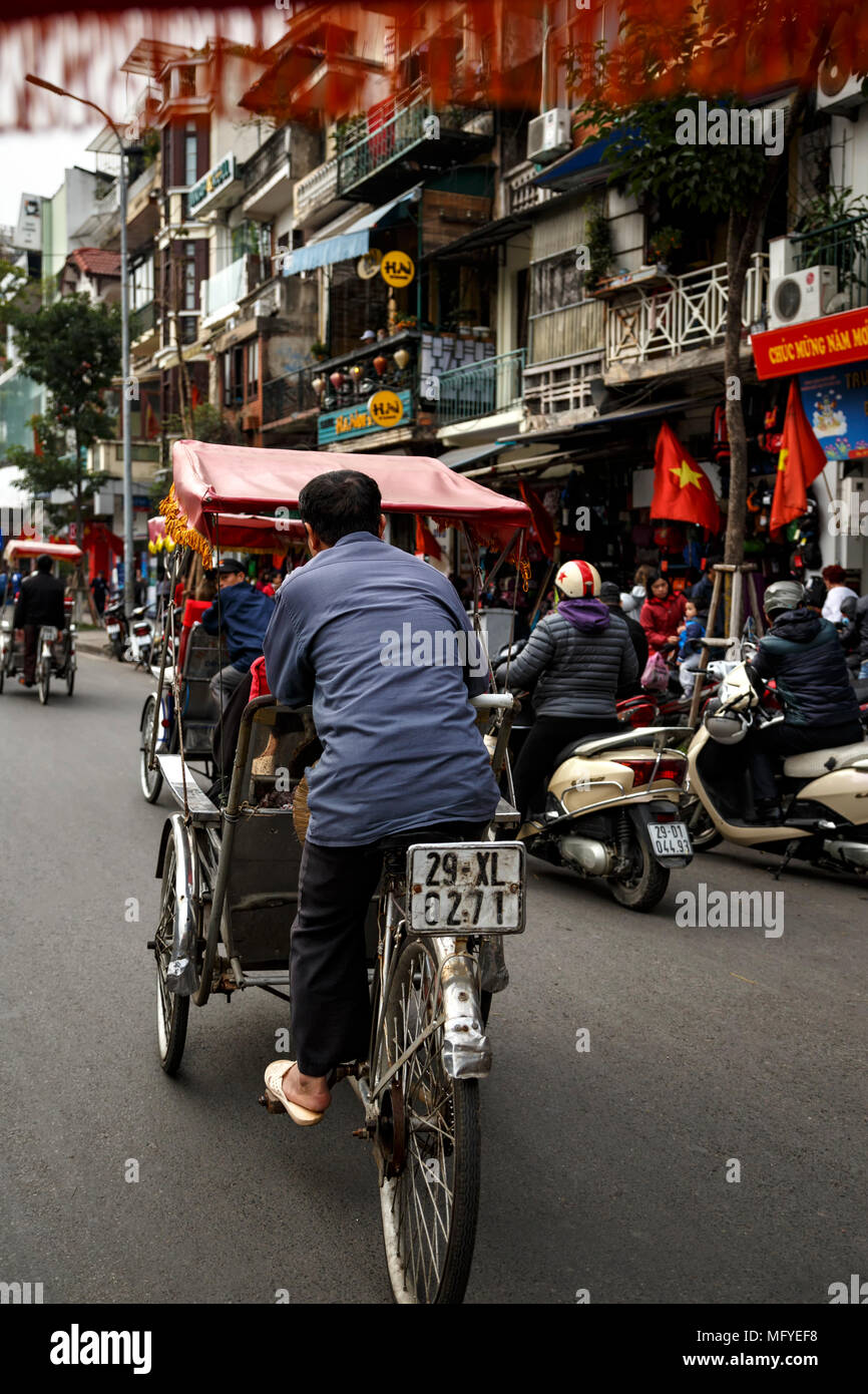 Cyclo (three-wheel bicycle taxi) driver in traffic, Old Quarter, aka The 36 Streets, Hanoi, Vietnam - Stock Image