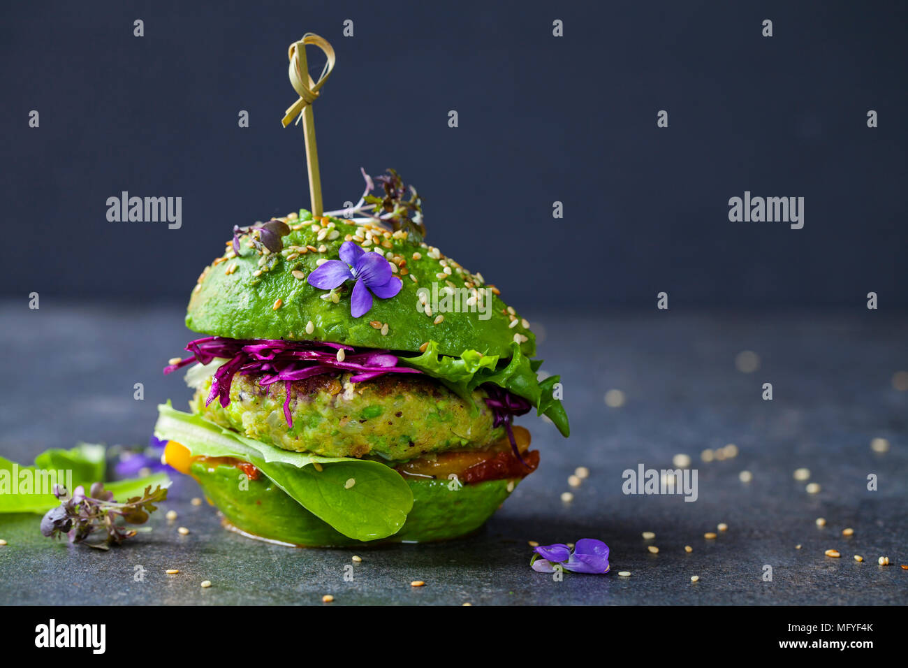 Avocado sandwich with green vegan burger,  roast yellow pepper and pickled red cabbage - Stock Image