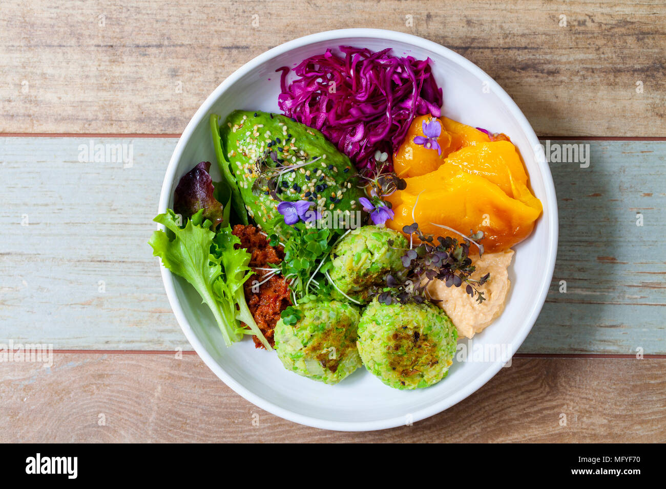 Vegan Buddha bowl with beans and green peas patties, avocado, roast yellow pepper, red cabbage, sundried tomato paste and hummus - Stock Image