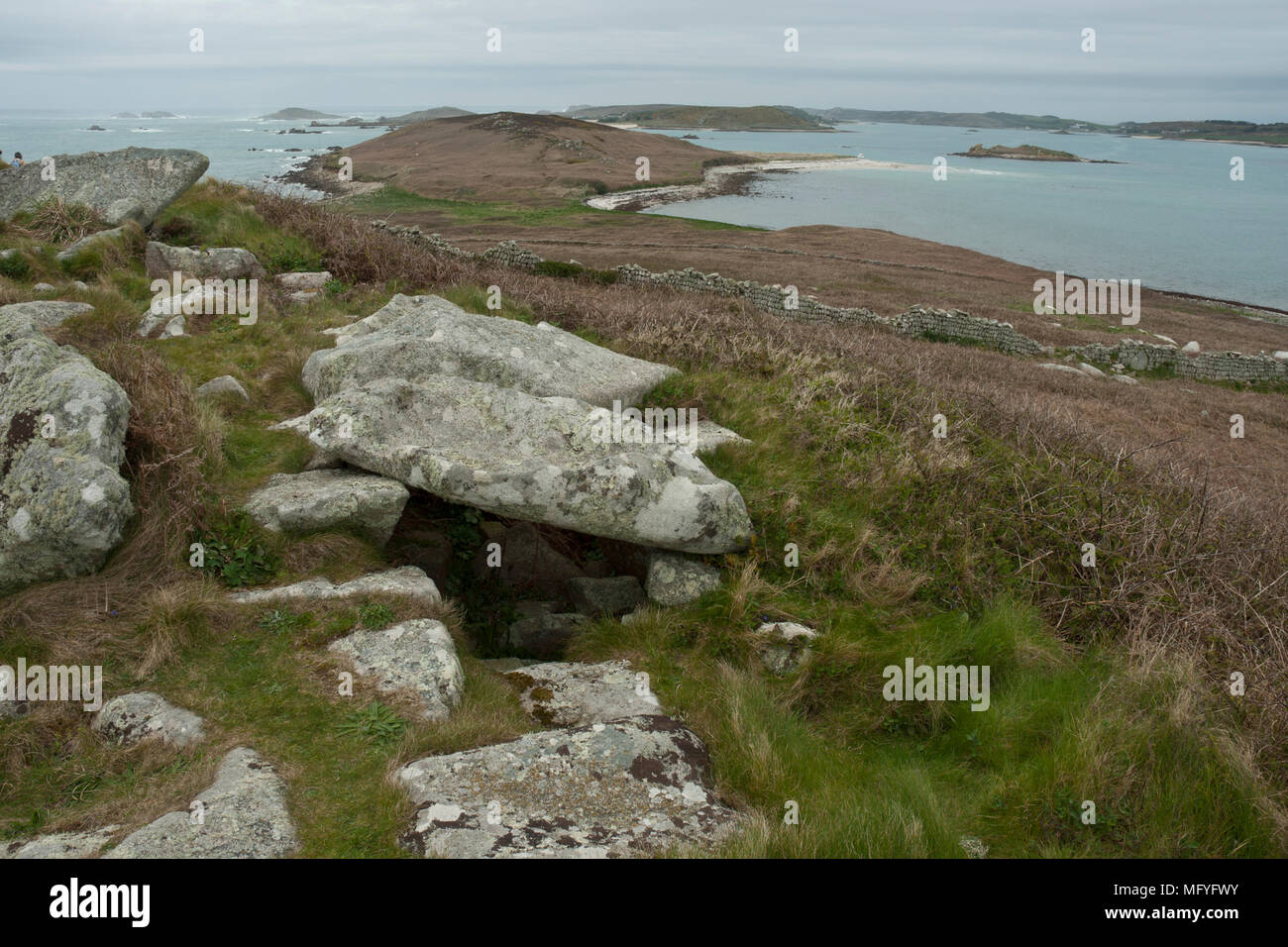 A prehistoric entrance grave with capstones in the foreground with Samson Island and the sea beyond in the background. - Stock Image
