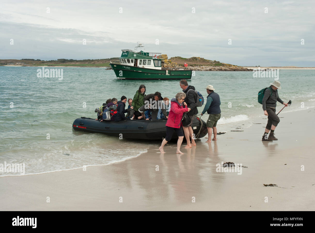 Group of tourists disembarking from ferry, via a dinghy, onto Samson Island , Isles of Scilly - Stock Image