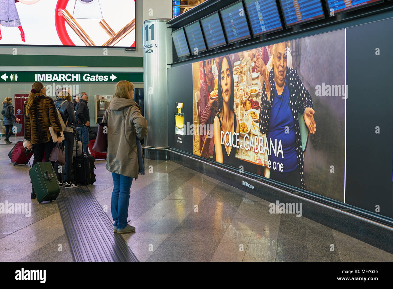 MILAN MALPENSA, ITALY - CIRCA NOVEMBER, 2017: passengers standing in front of the flight information display monitors at Milan-Malpensa airport. - Stock Image
