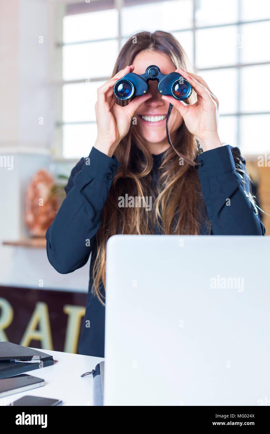 Deutschland, München, Portrait Geschäftsfrau im Büro vor Laptop durch Fernglas schauend Stock Photo