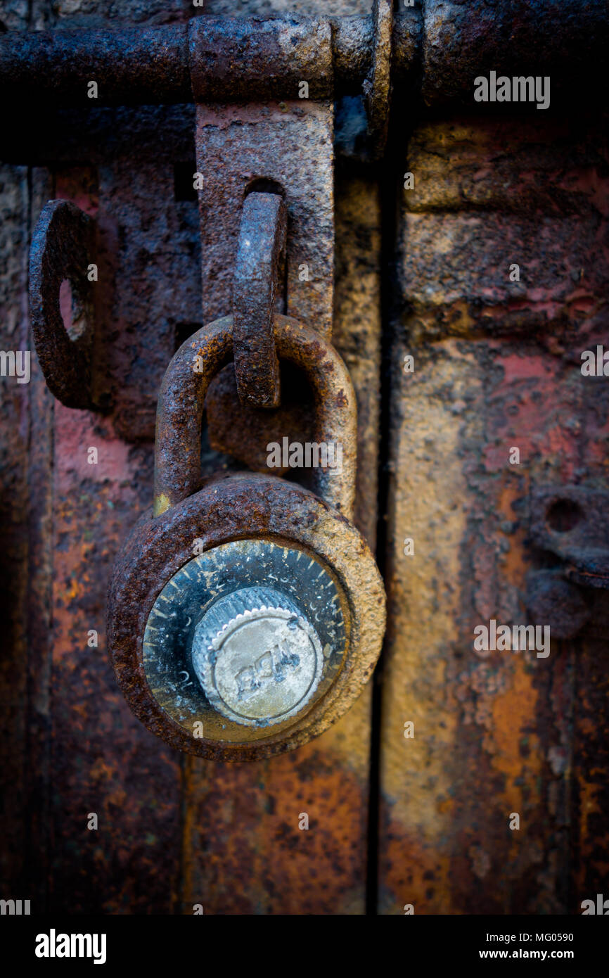 A rusted combination lock on a graffiti-covered metal door - Stock Image