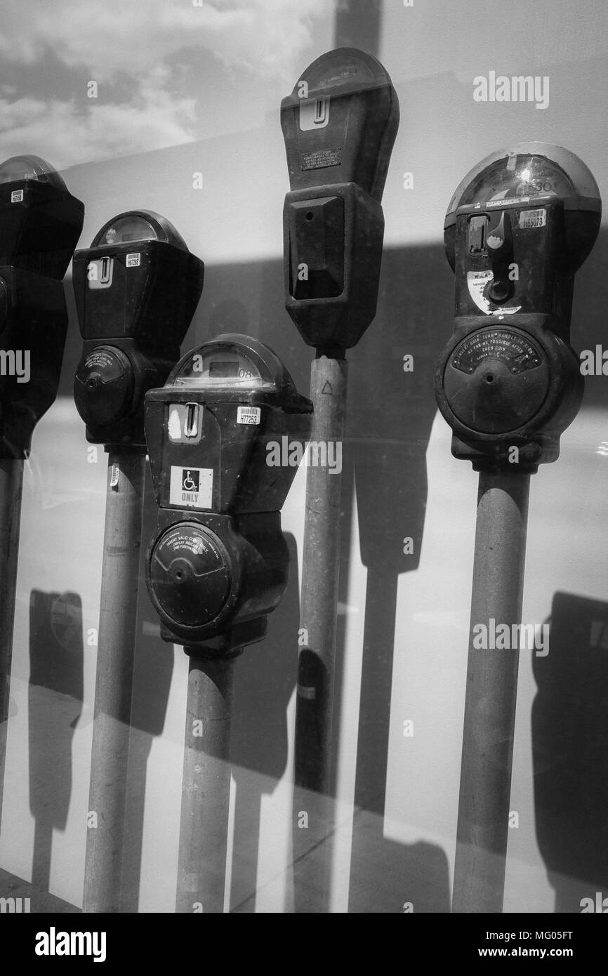A black and white image of a display of parking meters - Stock Image