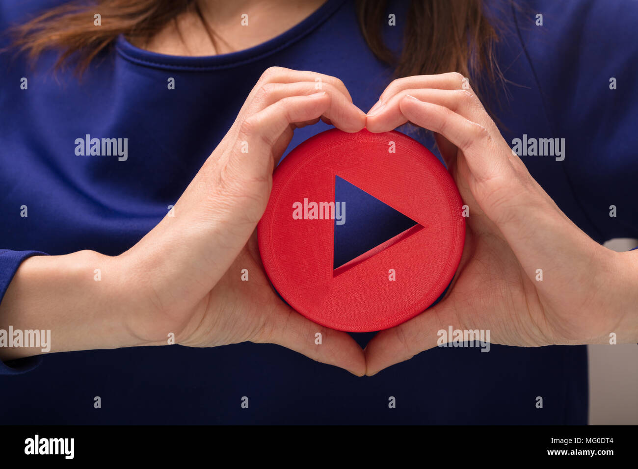 Woman's Hand Making Heart Shape With Her Hand Holding Play Icon Stock Photo