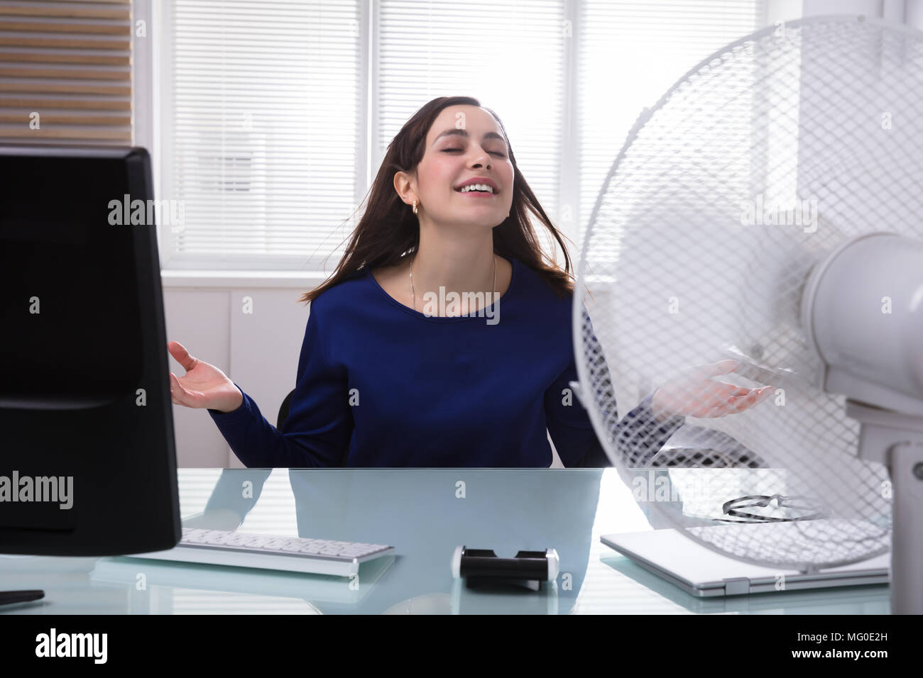 Smiling Young Businesswoman Cooling Herself With Electric Fan During Hot Weather - Stock Image