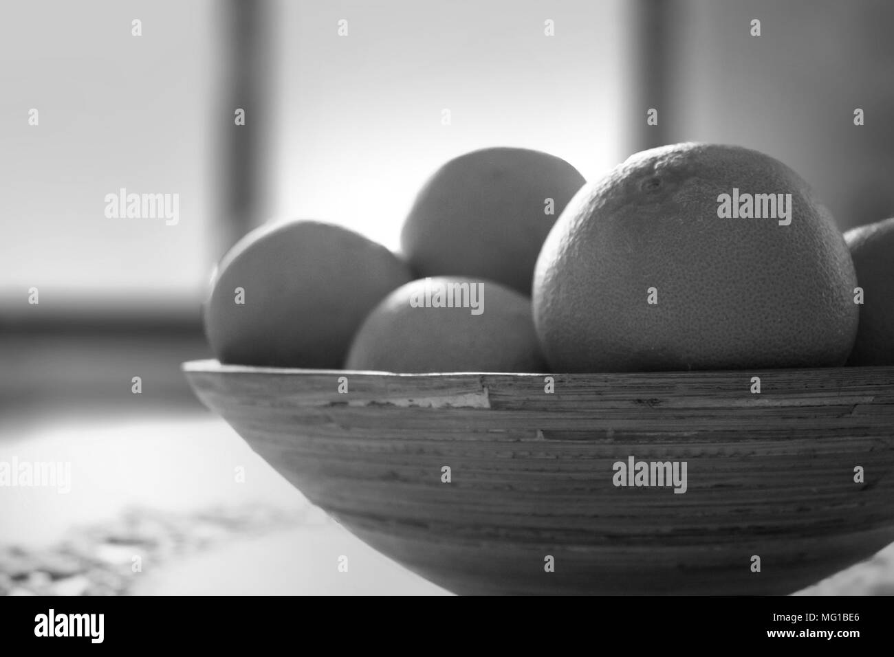 Close up of oranges with blurred background in black and white. - Stock Image