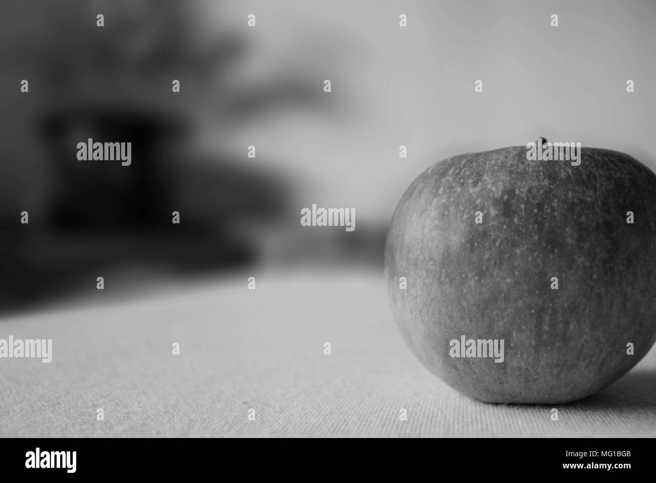 Close up of a red apple with blurred background in black and white. - Stock Image