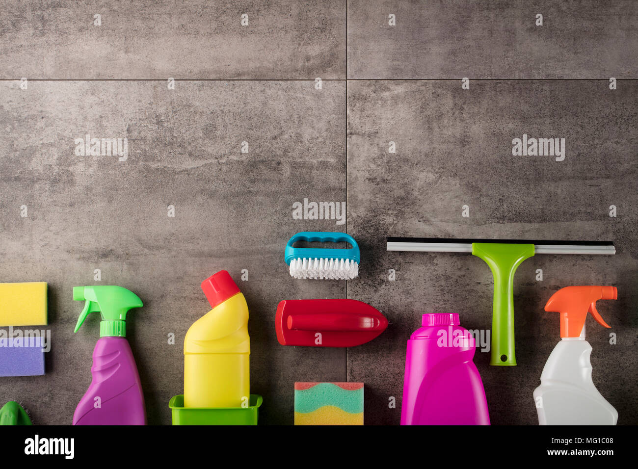 Spring cleaning concept. Colorful cleaning products on gray tiles. Place for typography. - Stock Image