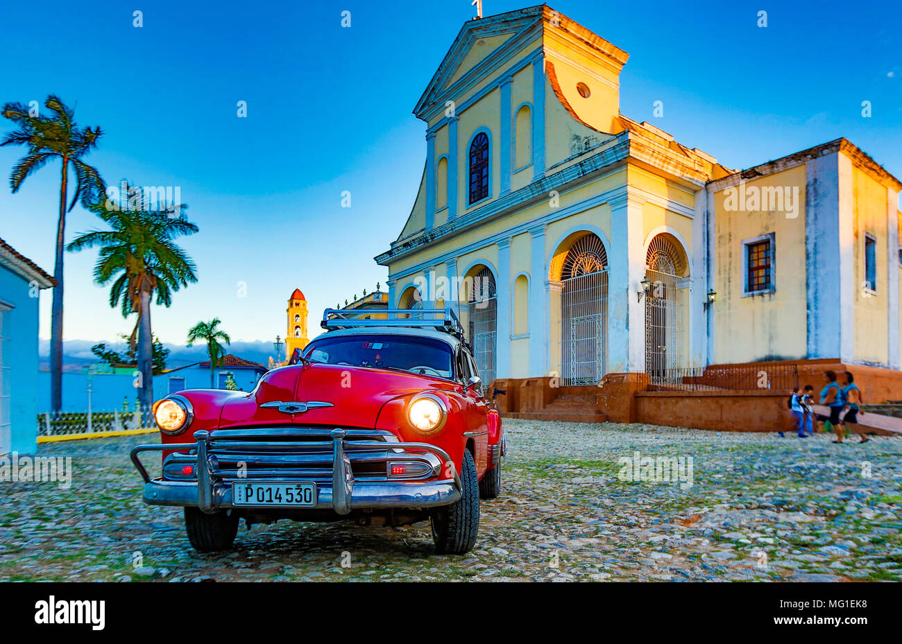 Trinidad, Cuba, Nov 28, 2017 - Red Classic 1950's Chevrolet is parked in front of a church - Stock Image