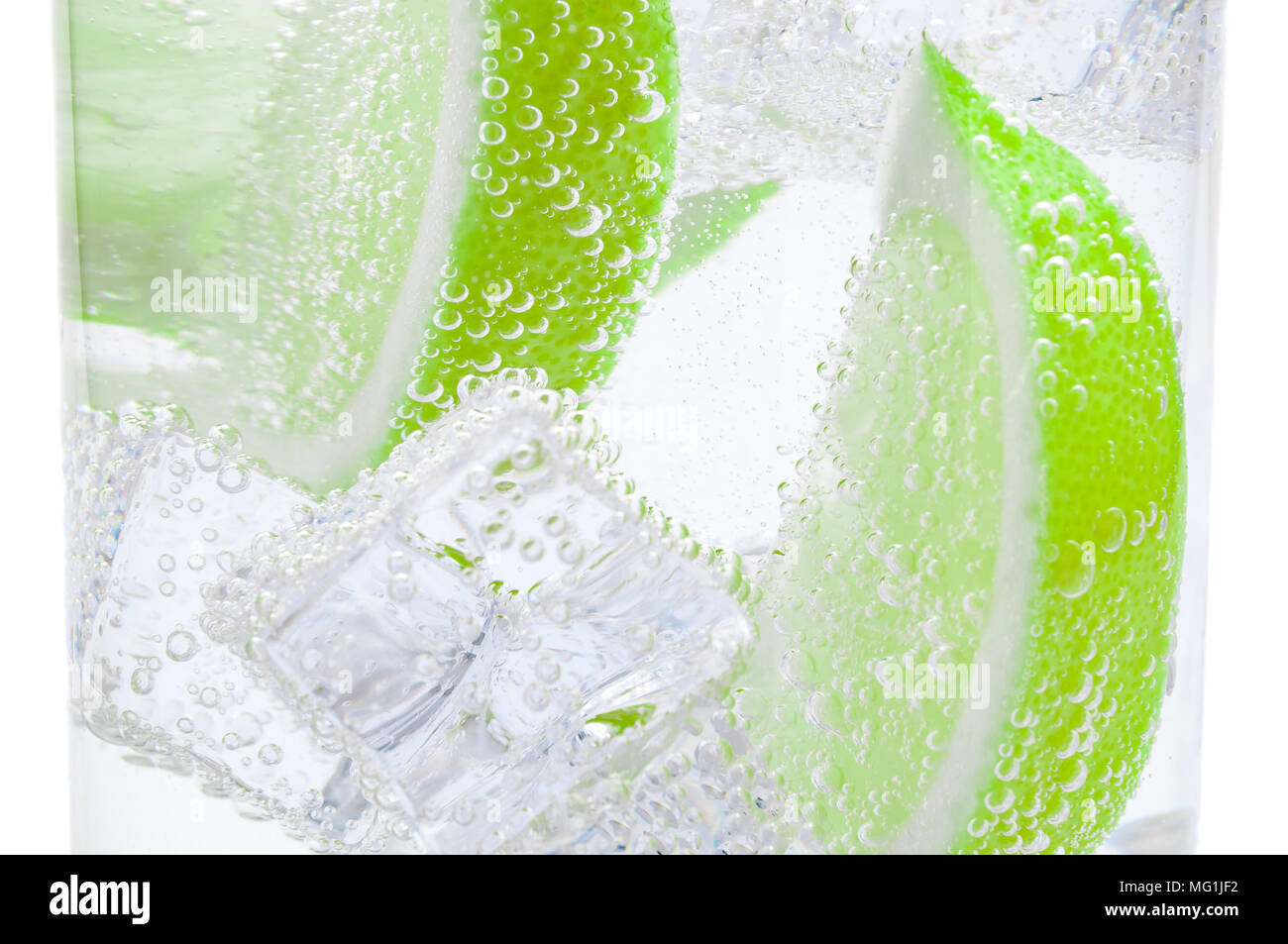 Pieces of fresh juicy lime sink into crystal clear water. - Stock Image