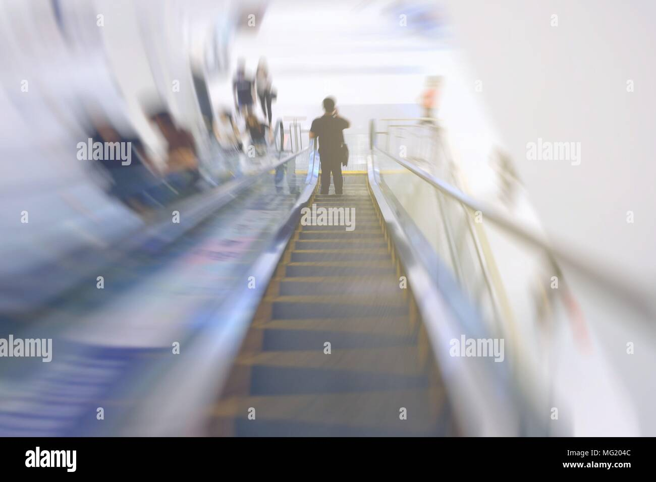Motion Blurred Image of Man Hoding Moblie Phone and Standing on Escalator. Stock Photo