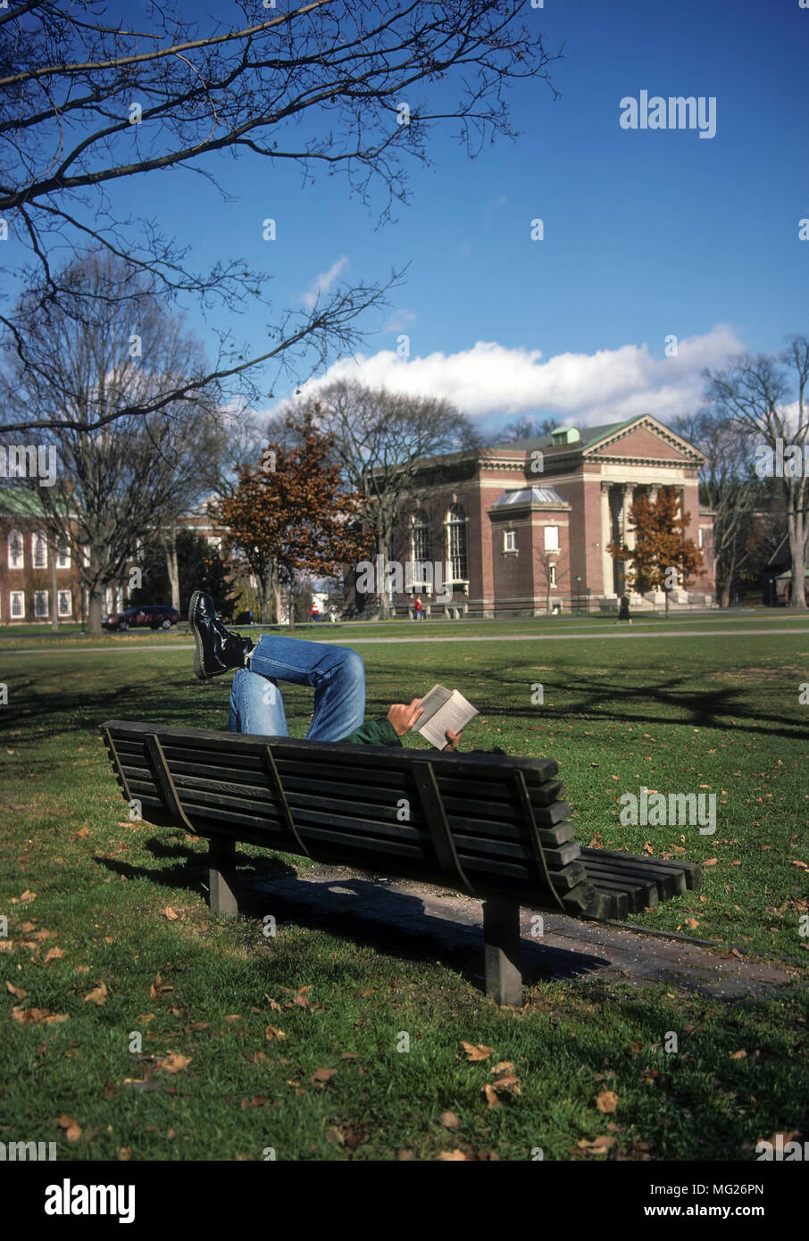 "A student at Dartmouth College lays on a park bench located on ""The Green"" reading a book at Hanover, New Hampshire, United States, North America. Stock Photo"