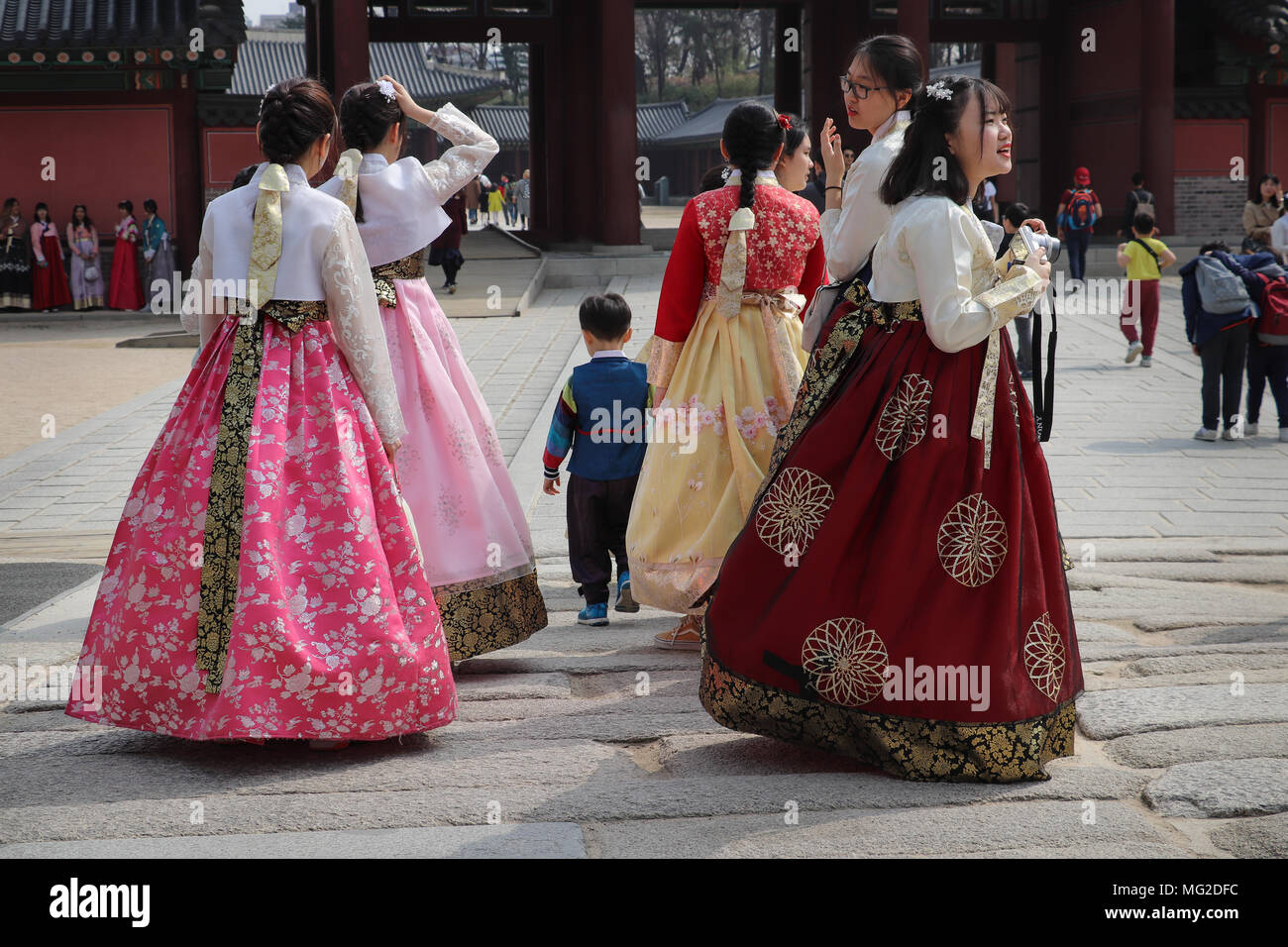 Group of several Korean teen girls (+ 1 boy) dressed in colorful traditional fullskirted hanboks visit the Changdeokgung Palace in Seoul,South Korea. - Stock Image