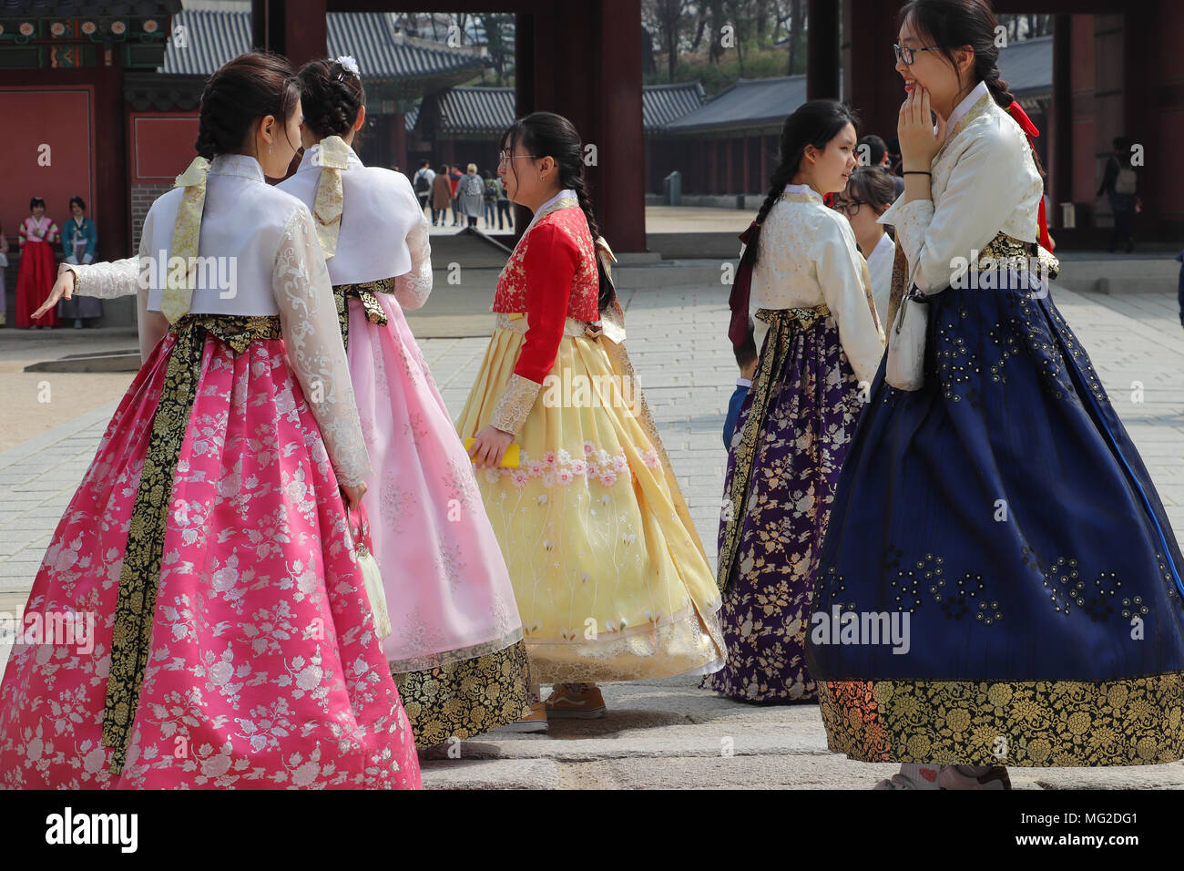 Group of several Korean teenage girls dressed in colorful traditional full-skirted hanboks visit the Changdeokgung Palace in Seoul, South Korea. - Stock Image