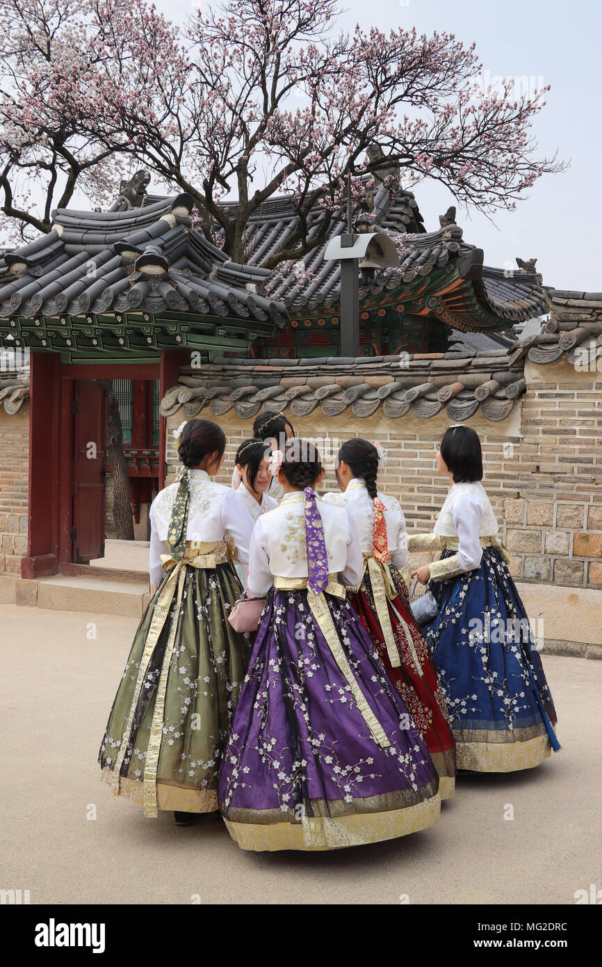 Group of six Korean teenage girls in colorful fullskirted traditional hanbok dress gather near a blooming cherry tree at Changdeokgung Palace in Seoul - Stock Image