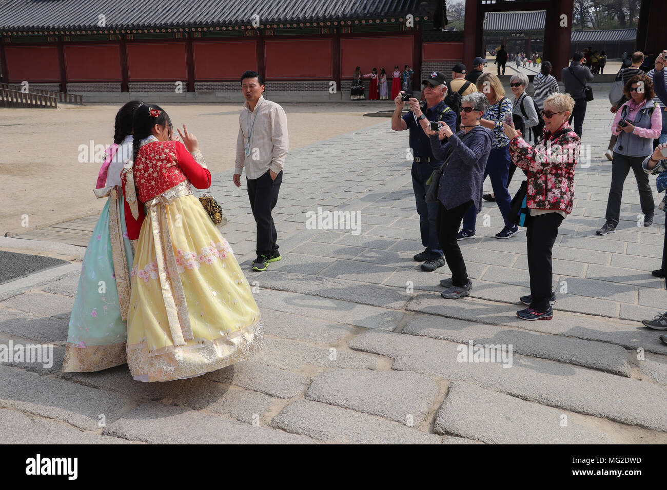 A group of tourists rush over to photograph two young women dressed in traditional brightly colored Korean hanboks who pose in Seoul, Korea. - Stock Image
